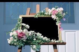 Красивая фоторамка для одной фотографии выполненная в романтическом стиле.  Деревянный мольберт стоящий рядом с голубой дверью. Мольберт украшен композицией из цветов. Эта фоторамка для фотошопа идеально подойдёт нежной девушке, которая хочет сделать подарок своему возлюбленному.