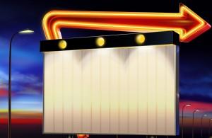 Рекламный щит стоит посреди трассы под лучами заходящего солнца.
